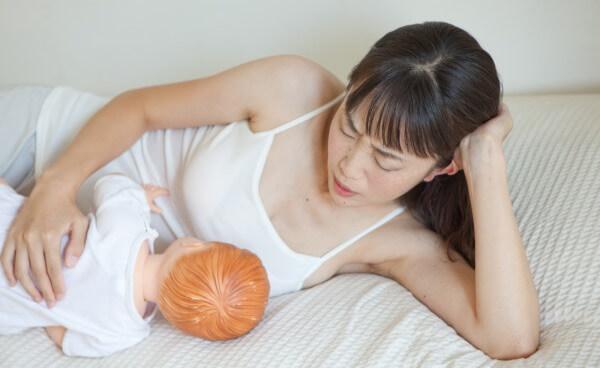 写真:添い乳の姿勢で首、肩、背中、腰など体が疲れる、つらい